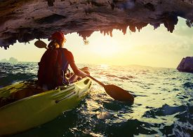stock photo of kayak  - Young lady paddling the kayak from limestone cave towards open sea - JPG
