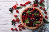 stock photo of blackberries  - Salad of cherry raspberry currant and blackberry in a wooden bowl on the table - JPG