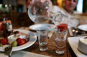 pic of vodka  - Man fills glasses of vodka in the pub - JPG