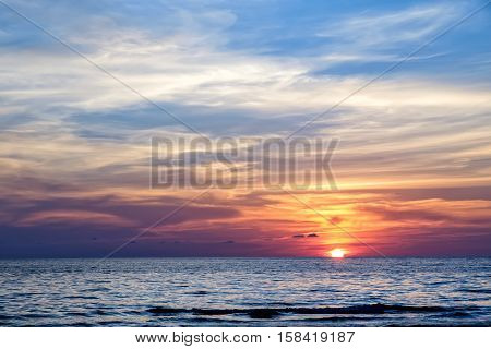 poster of Coast of the sea at colorful sunset Koh Chang, Thailand. Beach sunset is a golden sunset sky with a wave rolling to shore as the sun sets over the ocean horizon