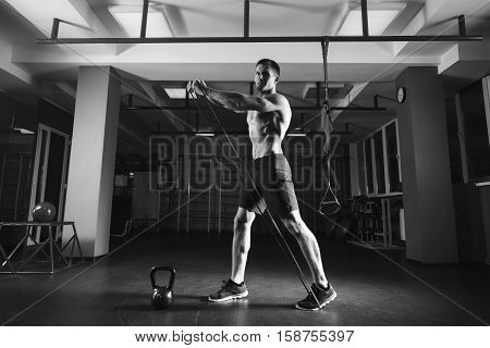 poster of Fitness man exercising with stretching band in the gym. Muscular sports man exercising with elastic rubber band. Guy working out with rubber band. Fit, fitness, exercise, workout and healthy lifestyle
