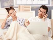 Young couple in bed, man using laptop and mobile, woman bored.