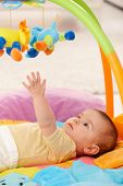 stock photo of playmates  - Baby reaching for colorful toy on playmat - JPG