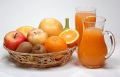 stock photo of fruit-juice  - various fresh fruits in a basket and multivitamin juice in a jug - JPG