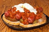 picture of hot dogs  - Three Chili dogs on top of potatoes and bread covered in Sour Cream Hot Sauce and Pepper - JPG