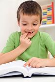 picture of dyslexia  - Stressed elementary school boy with reading problems trying to remember - JPG