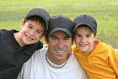 stock photo of happy kids  - Dad and Boys in their baseball uniforms - JPG