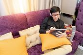 Young Asian Happy Man With Headphones And Eyeglasses Using Digital Tablet And Pen On Sofa In Living  poster
