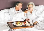 Couple having breakfast in bed poster
