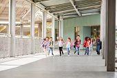 Primary school kids run holding hands in school corridor poster