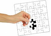 The Missing Piece Of The Jigsaw - Female Hand Holding A Piece Of Jigsaw Against A Jigsaw Puzzle With poster