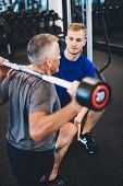 Personal trainer and senior man exercising at the gym. Gym assistant. Weightlifting. poster