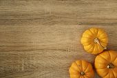 Orange Color Three Ripe Pumpkins With Stem On Light Brown Wooden Table poster
