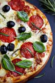 Pizza with salami, mozzarella, black olives, spices, fresh basil and rosemary. Italian pizza. Dark s poster