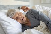 Old woman sleeping on bed at home with her husband. Elder lady sleeping in the bedroom with husband  poster