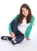 Cute Teenage Girl With Blue Eyes Sits On Floor