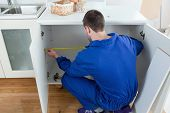 foto of formica  - Repair man measuring something in a kitchen - JPG