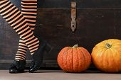 Happy Halloween! Female Feet In Stockings With An Orange Pumpkin poster