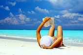 stock photo of girl reading book  - Young women is reading on the coral beach Maldives - JPG