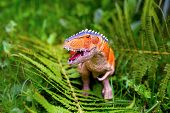 A Predatory Dinosaur With Huge Teeth Among The Ferns. A Figurine Of A Dinosaur poster