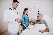 Doctor With Patient.old Man Lies In Hospital. Sick Man In Clinic. Doctor And Patient. Young Doctor W poster