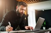 Young Bearded Businessman Is Standing By Computer, Looking At Laptop Screen, Making Notes In Noteboo poster