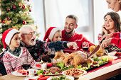 Senior Woman Cutting Turkey For Christmas Dinner With Happy Family At Home poster