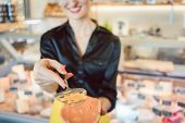 Beautiful woman offering cheese on delicatessen counter cutting a test bit off poster