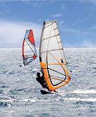 stock photo of wispy  - A pair of windsurfers on a highlighted sea with blue sky and wispy clouds - JPG