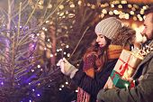 Adult couple shopping for Christmas tree in the city during Christmas time poster