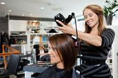 stock photo of barber  - Beautician blow drying woman - JPG