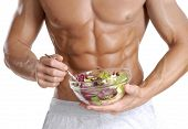 stock photo of discipline  - Shaped and healthy body man holding a fresh salad bowl - JPG