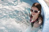 stock photo of hot-tub  - A preteen girl enjoying an outdoor hot tub on a sunny day - JPG