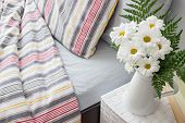 foto of pillowcase  - Bright bedroom decorated with a bouquet of white flowers - JPG