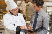stock photo of catering service  - Waiter and chef discussing the menu in the kitchen - JPG
