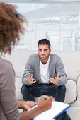 stock photo of she-male  - Man speaking to a therapist while she is taking notes - JPG