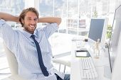 stock photo of mannequin  - Smiling designer at his desk in bright modern office - JPG