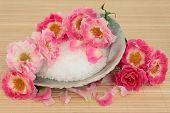 Rose flower spa arrangement with sea salt in an abalone shell and sponge over bamboo background. Car