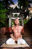 picture of ashtanga vinyasa yoga  - Yoga meditation in baddha padmasana pose by man in white trousers at stone temple background in tropical forest - JPG