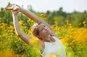 picture of ragweed  - Caucasian blonde woman stretching in yogo pose in the middle of a meadow of ragweed flowers - JPG