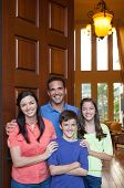 image of entryway  - Hispanic father caucasian mother and mixed ethinicity son and daughter standing in entryway beside large wooden door of large home living room with tall windows in background - JPG