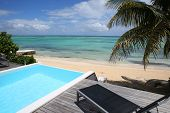 image of infinity pool  - Infinity pool with deck chair by the beach - JPG