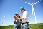 picture of turbines  - Engineers looking at wind turbine site with tablet - JPG