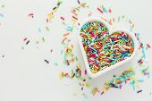 stock photo of sprinkling  - Heart shaped cookie cutter with candy sprinkles - JPG