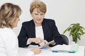stock photo of only mature adults  - Mature woman having a meeting with financial advisor in the office - JPG