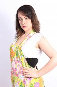 stock photo of partially clothed  - Pretty young woman with a colorful apron partially covering her white - JPG