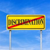 pic of racial discrimination  - Word discrimination written on yellow street sign and crossed off - JPG