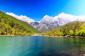 stock photo of jade  - A view of a river and Jade Dragon Snow Mountain in Lijiang  - JPG