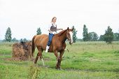 stock photo of bareback  - Beautiful blonde woman riding horse bareback and without bridle - JPG