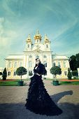stock photo of evil queen  - Beautiful woman in black dress posing next to the palace - JPG